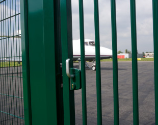 LSKZU2_SSKZ__Airplane_behind_green_sliding_gate__1920px